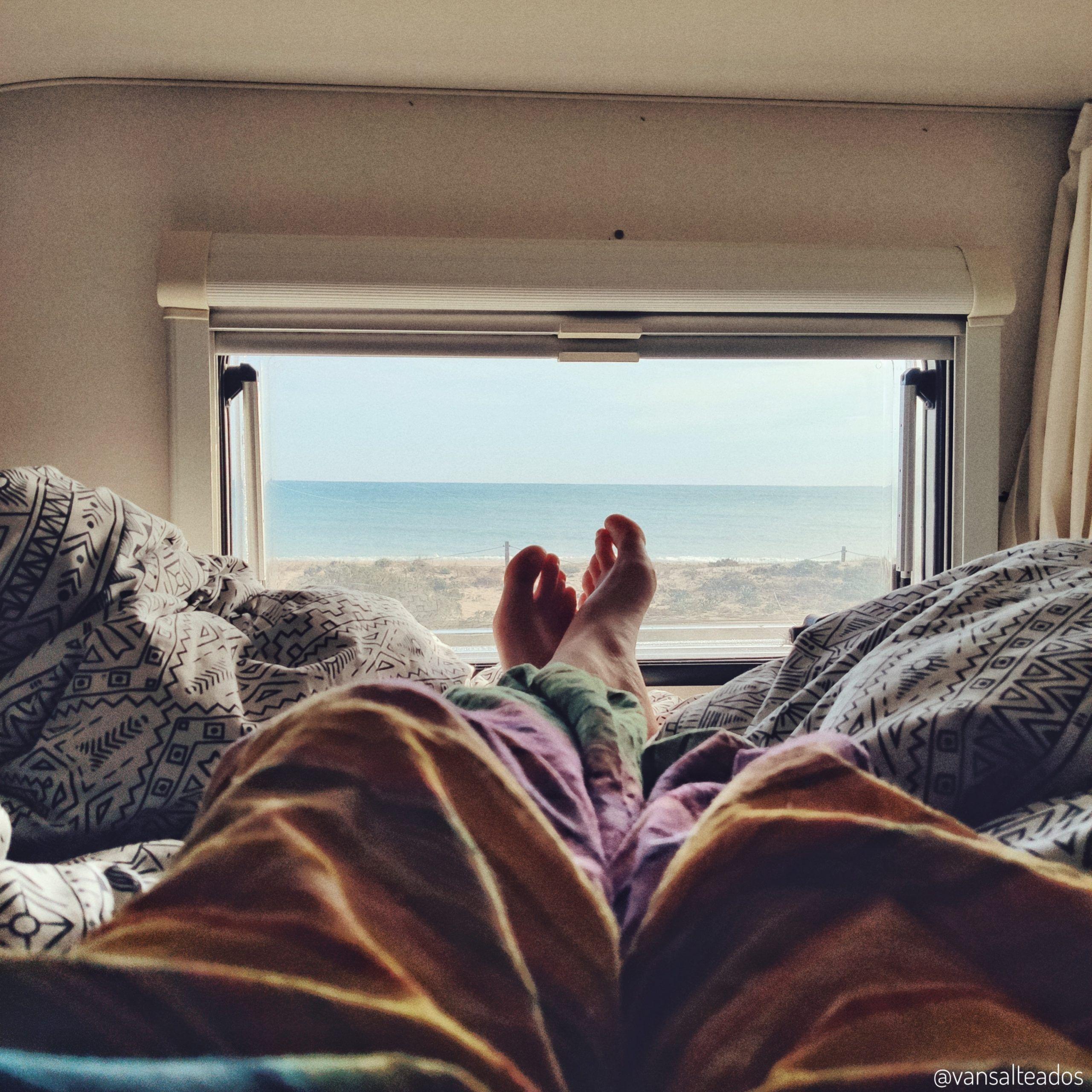 tumbado en la cama de una autocaravana mirando el paisaje